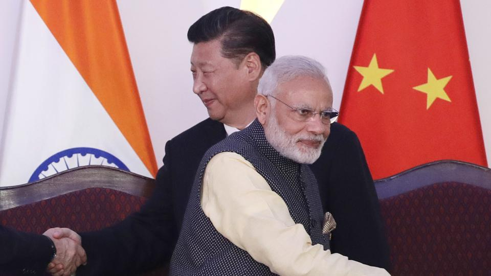 Prime Minister Narendra Modi, front and Chinese President Xi Jinping shake hands with leaders at the BRICS summit in Goa, India.