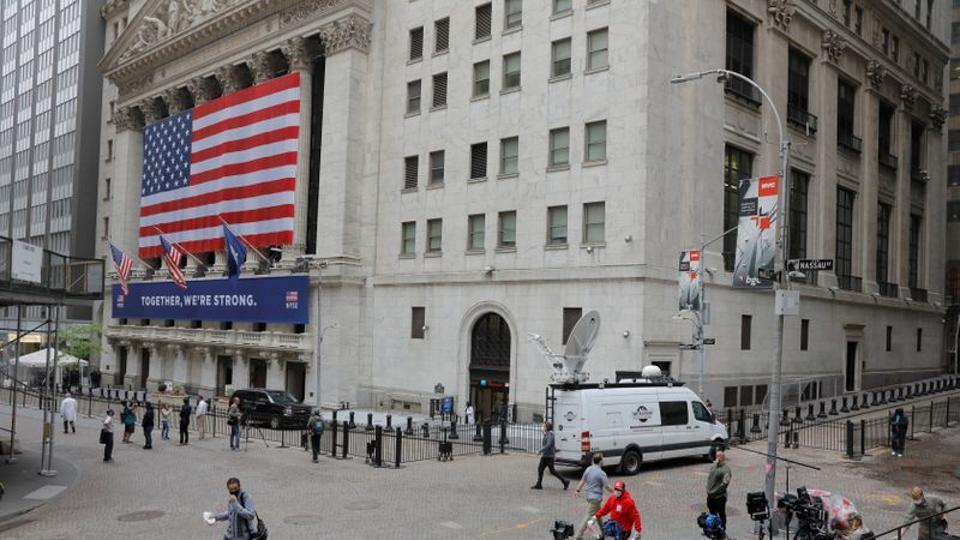 Members of the media report outside of the New York Stock Exchange as the building opens for the first time since March while the outbreak of the coronavirus disease continues in the Manhattan borough of New York, US.