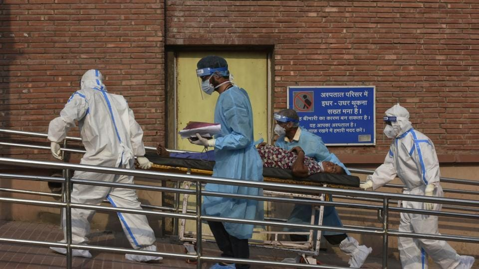 Medical professionals wearing PPE coveralls escort a patient suspected of coronavirus infection into the the Covid-19 ward at LNJP Hospital in New Delhi.