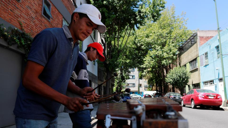 Musicians play the marimba on the streets in a residential neighbourhood to earn a living as they serenade homes for tips in Mexico City.