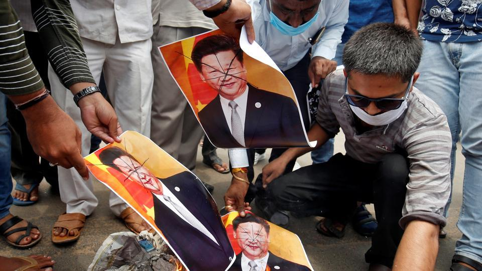 Supporters of India's ruling Bharatiya Jayanta Party (BJP) burn defaced posters of Chinese President Xi Jinping during a protest against China, in Ahmedabad, India.