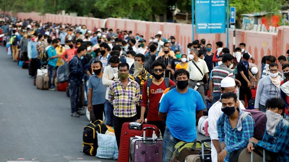 Migrant workers and their families wait in lines outside a railway station to board a train to their home state.