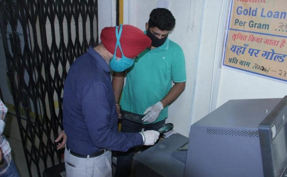 Forensic experts looking for clues at the Union Bank of India ATMin Kishangarh village, Chandigarh, on Thursday.