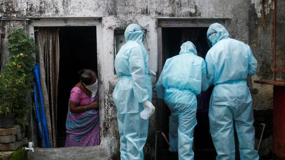 A woman watches as healthcare workers check the temperature of residents of Dharavi slum in Mumbai, onWednesday.