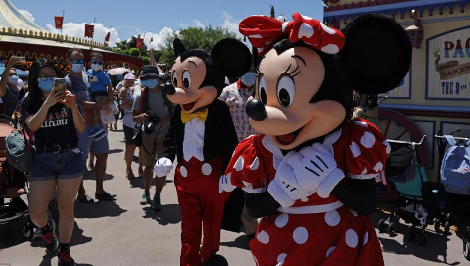 The iconic cartoon characters Minnie and Mickey Mouse walk with the visitors at the Hong Kong Disneyland on Thursday, June 18, 2020.