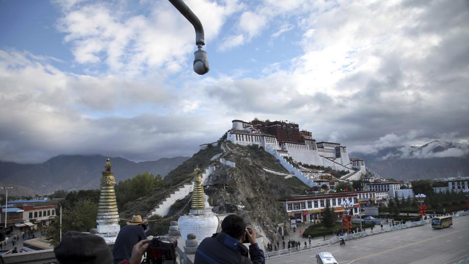Tourists take photos of the Potala Palace beneath a security camera in Lhasa, Tibet. The railway project is part of the 435-km railway project linking Lhasa and Nyingchi, also known as Linzhi, in southwest China's Tibet Autonomous Region (TAR).