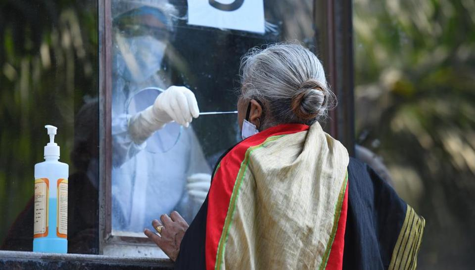 A medical professional collects a swab sample from a woman to test for COVID-19 infection at Swami Parmanand Prakritik Chikitsalaya Yoga & Anusandhan Kendra in West Vinod Nagar, New Delhi.