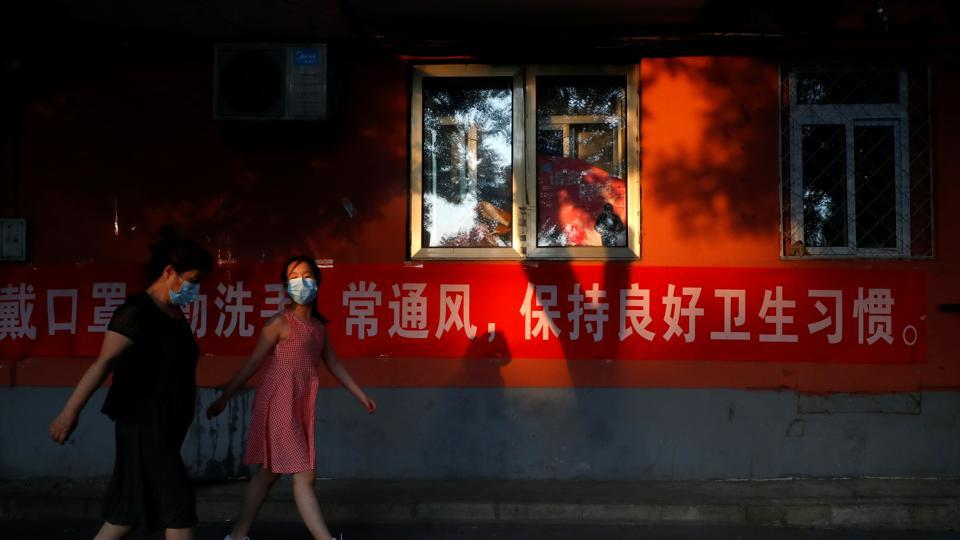 People wearing protective masks walk past a public health announcement banner, after a new outbreak of the coronavirus disease (COVID-19), in Beijing, China.