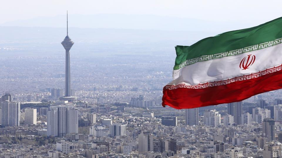 Iran's national flag waves as Milad telecommunications tower and buildings are seen in Tehran, Iran.
