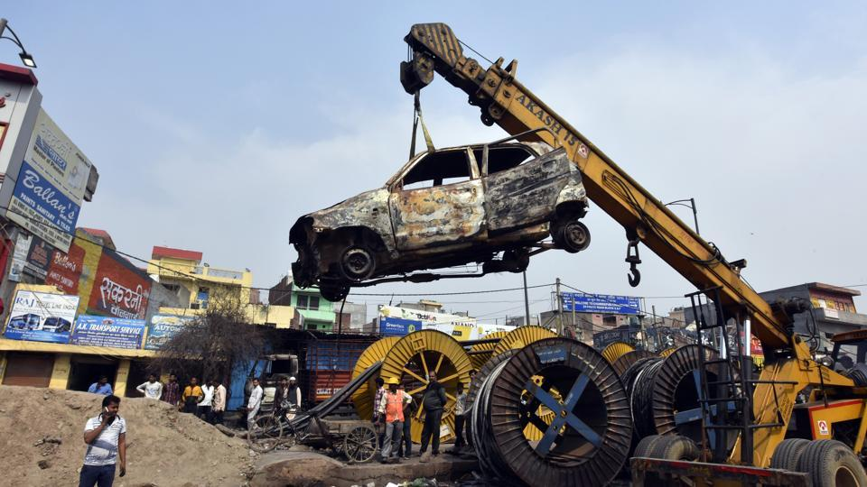 Charred vehicles are carried using a crane following violent clashes in North East Delhi over the new citizenship law, at Chand Bagh, in New Delhi.