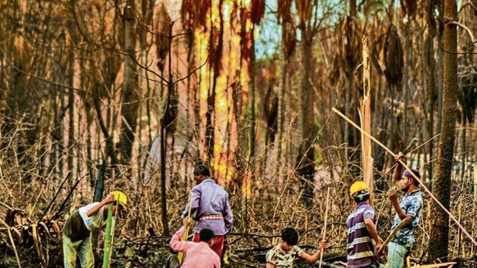 Workers build a structure near the gas well blowout site in Baghjan in Assam's Tinsukia district.