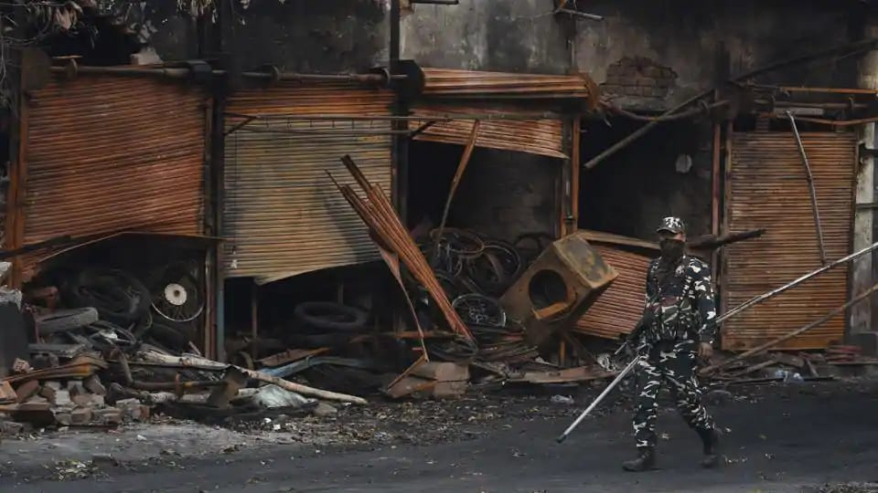 Sashastra Seema Bal (SSB) personnel walk past burnt and damaged shops, which were allegedly set on fire by miscreants during communal violence last week.(Sanchit Khanna/HT PHOTO)
