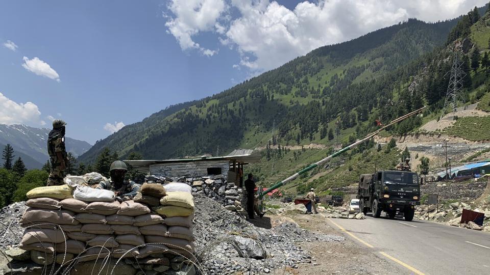 Indian paramilitary soldiers keep guard as Indian army convoy moves on the Srinagar- Ladakh highway at Gagangeer, north-east of Srinagar.