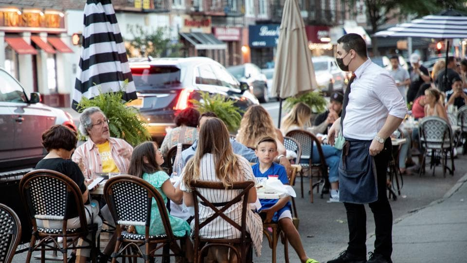 People dine in parking spaces on the street outside CEBU restaurant on the first day of the phase two re-opening of businesses following the outbreak of the coronavirus disease (Covid-19) in Brooklyn, New York.