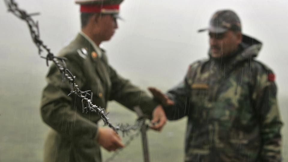 Chinese soldier and an Indian soldier put into place a barbed wire fence removed temporarily for Chinese officials to cross back to their country at Nathula Pass, in northeastern Indian state of Sikkim.