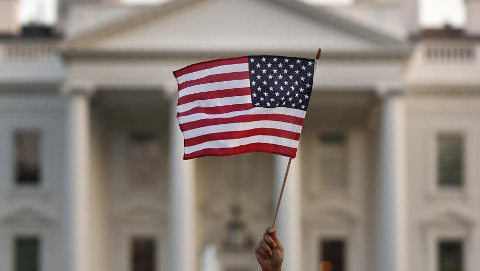 A flag is waved outside the White House in Washington. The Trump administration is extending a ban on green cards issued outside the United States until the end of 2020 and adding many temporary work visas to the freeze.