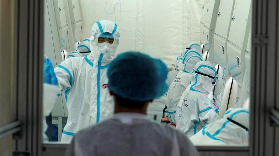 Staff members in protective suits work inside a mobile laboratory for nucleic acid testing, at a sports centre in Daxing district following a new outbreak of the coronavirus disease (COVID-19) in Beijing, China June 23, 2020.