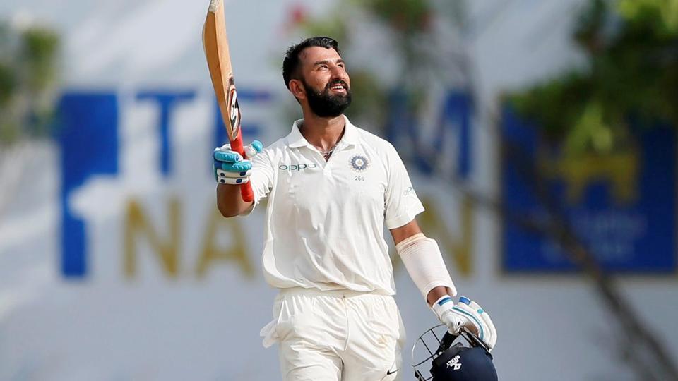 India's cricketer Cheteshwar Pujara celebrates his century.