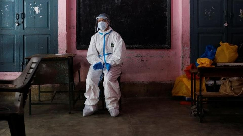 File photo: A medical worker sits inside a classroom as she takes a break at a school which was turned into a centre to conduct tests for the coronavirus disease in New Delhi.