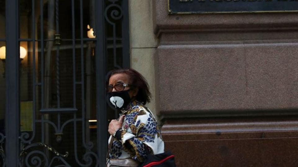 A woman wearing a protective face mask walks in front of Banco do Brasil (Bank of Brazil) cultural building during the coronavirus disease (Covid-19) outbreak in Sao Paulo, Brazil.