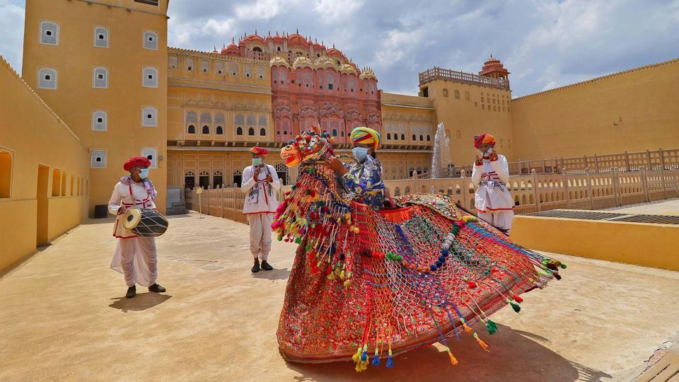 Rajasthani folk artists perform to spread awareness about Covid-19 at Hawa Mahal after the state government permitted to reopen tourist places in Jaipur on Tuesday.