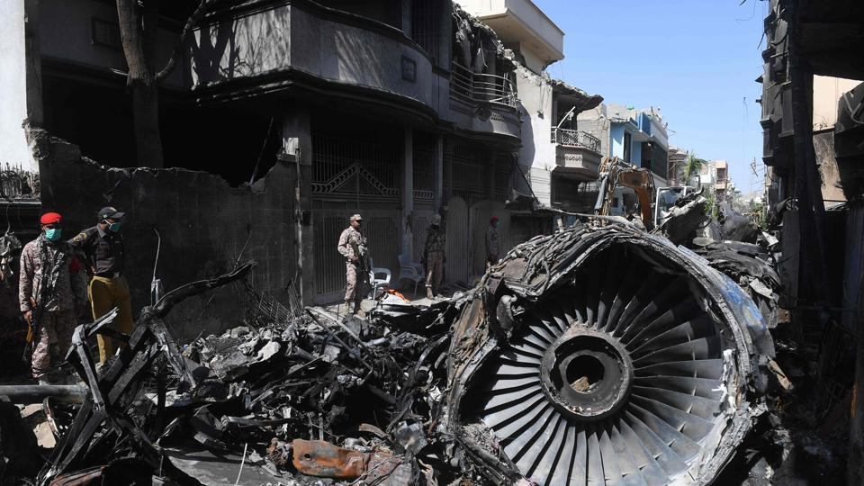 In this photo taken on May 24, 2020, security personnel stand beside the wreckage of a plane at the site after a Pakistan International Airlines aircraft crashed in a residential area days before, in Karachi.