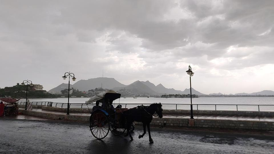 A horsecart is seen in the backdrop of Anna Sagar Lake with dark monsoon clouds in the sky, in Ajmer , Rajasthan.
