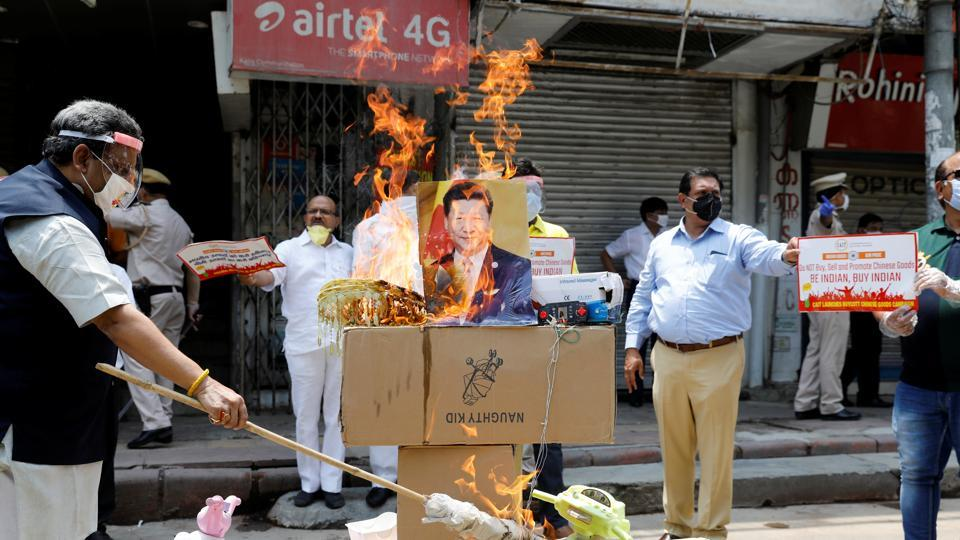 Demonstrators burn products made in China and a defaced poster of Chinese President Xi Jinping during a protest against China, in New Delhi.