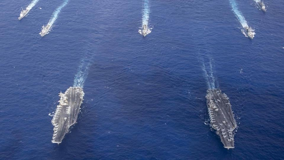The Theodore Roosevelt Carrier Strike Group transits in formation with the Nimitz Carrier Strike Group while conducting dual carrier and airwing operations in the Philippine Sea.