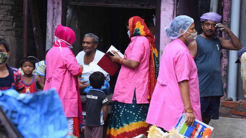 ASHA health workers talk to a man while conducting a door-to-door survey to identify Covid-19 cases, at JJ colony in Patparganj near Mayur Vihar in New Delhi on Thursday.