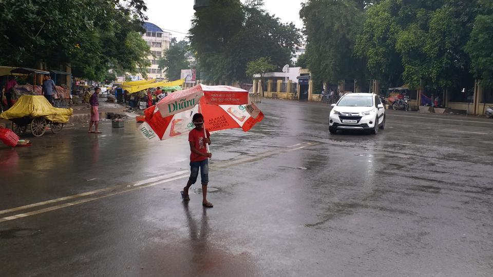 A child crossing the road with an umbrella as it rains, in Patna, Bihar on Thursday.