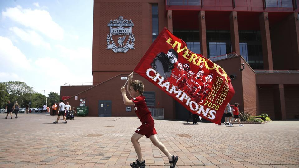 Liverpool fan Dillon Parry waves a flag outside Anfield in Liverpool, England, Friday June 26, 2020. Liverpool clinched its first league title since 1990 on Thursday, ending an agonizing title drought.