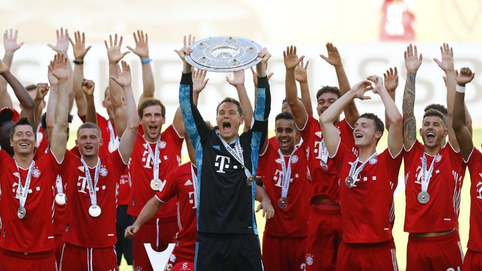 Bayern Munich's Manuel Neuer celebrates with the trophy and teammates after winning the Bundesliga.