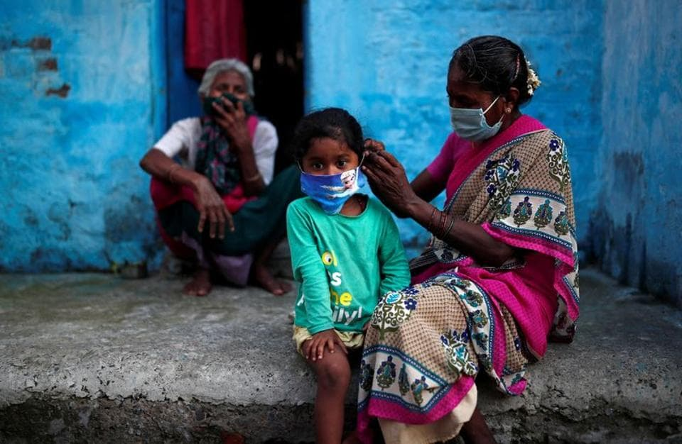 A woman wearing a protective face mask adjusts her daughter's face mask outside their house at a slum area, during an extended nationwide lockdown to slow the spreading of the coronavirus disease (Covid-19), in New Delhi.