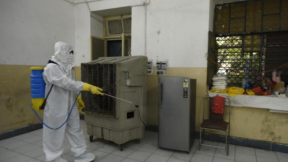 A health worker in PPE sanitizes the premises of a Covid-19 testing center in Karol Bagh.
