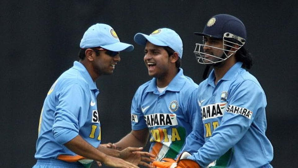 Indian cricket captain Rahul Dravid (L) is joined by Suresh Raina as they congratulate wicketkeeper Mahendra Dhoni