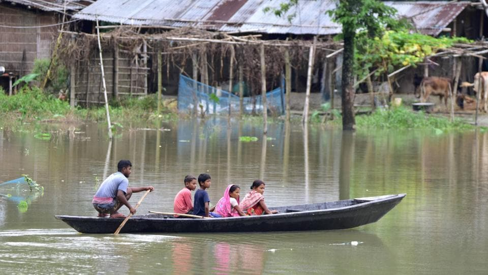 Locals cross a flooded area on a boat in Nagaon district, Assam, on June 27. With heavy rainfall continuing in most parts of the state, the flood situation in Assam has worsened. Over 2.53 lakh people have been affected in 16 of the state's 33 districts. (PTI)