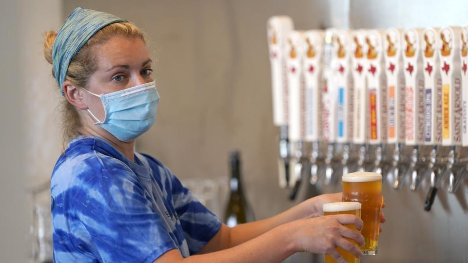 Bartender Katie McGranahan pours beers at the Saint Arnold Brewing Company Friday, June 26, 2020, in Houston.