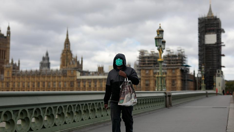 A commuter wearing a protective face mask crosses Westminster Bridge in view of the Houses of Parliament and Elizabeth Tower, also known as Big Ben, in London.