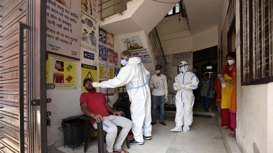 Health workers collect a Covid-19 test sample from a local resident, at Urban Primary Health Centre in Gurugram's Rajiv Nagar on Saturday.