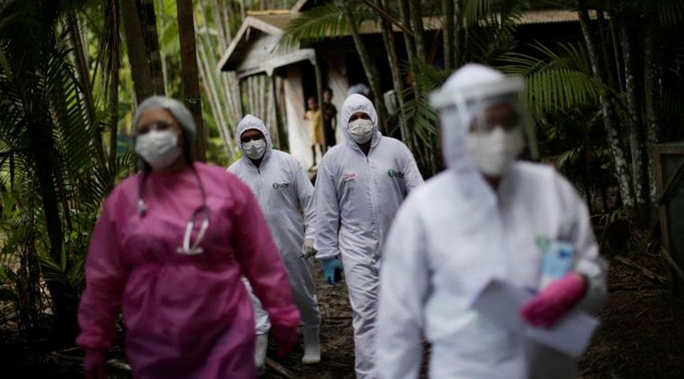 Healthcare workers walk in the riverside community Pinheiro to check on residents during the coronavirus disease outbreak, in the municipality of Portel in Brazil's Para state on June 6.