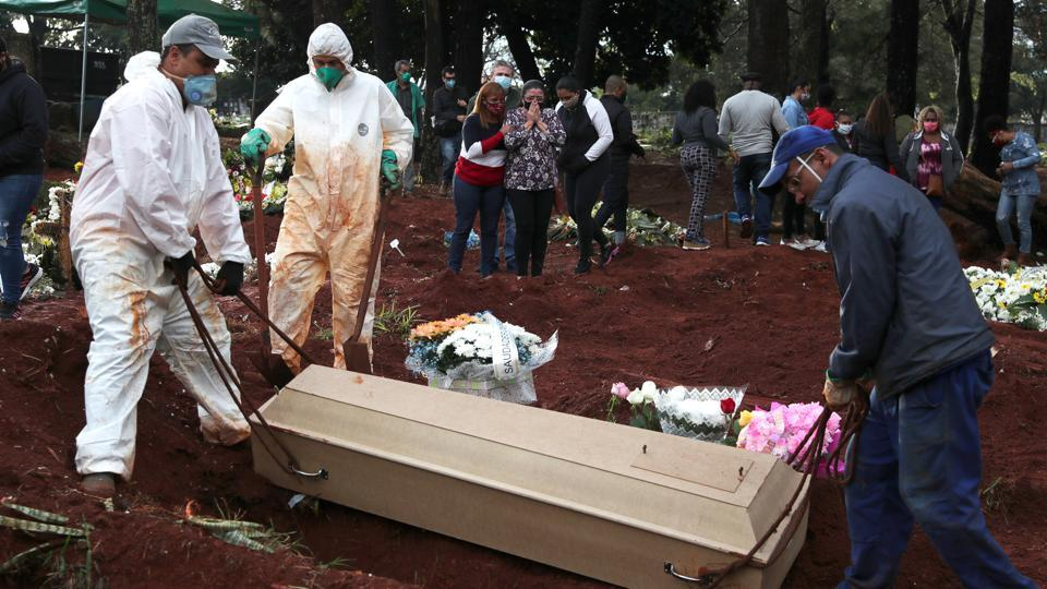 Relatives react as gravediggers bury the coffin of a person suspected to have died from the coronavirus disease at Vila Formosa cemetery, in Sao Paulo, Brazil.