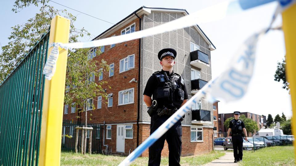 Police officers guard the block where the suspect of multiple stabbings allegedly lived, in Reading, Britain.