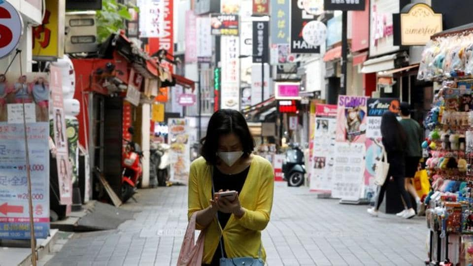 A woman wearing a mask looks at her mobile phone amid social distancing measures to avoid the spread of the novel coronavirus, in Myeongdong shopping district in Seoul, South Korea on May 28, 2020.