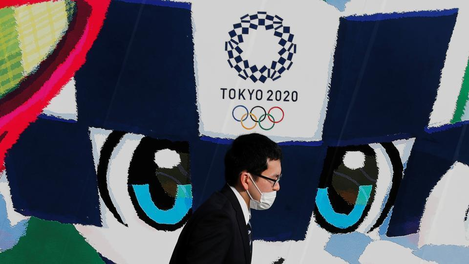 A man wearing a protective mask walks past a large poster featuring Tokyo 2020 Olympic Games mascot Miraitowa.