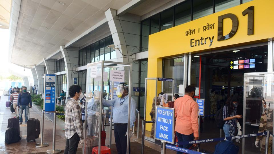 Passengers get their luggage sanitized and get thermal check up and show the registered Arogya sethu app ahead of boarding the flight at Pune Airport.