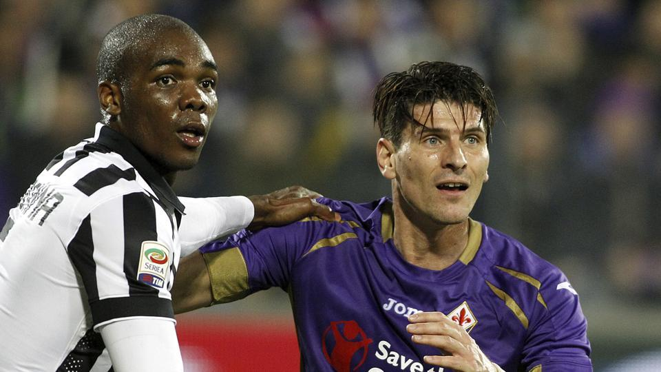 FILE - In a Friday Dec. 5 2014 file photo, Fiorentina's Mario Gómez and Juventu' Angelo Ogbonna hold each other during a Serie A soccer match at the Artemio Franchi stadium in Florence, Italy. Former Germany striker Mario Gómez has retired from soccer after scoring in his last game for Stuttgart. The soon-to-be 35-year-old says he has fulfilled his final wish – to help Stuttgart secure an immediate return to the Bundesliga after one season in the second division.(AP Photo/Fabrizio Giovannozzi, File)