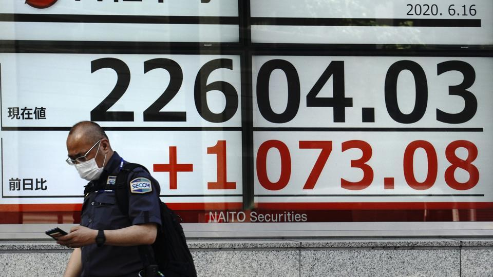 A man walks past an electronic stock board showing Japan's Nikkei 225 index at a securities firm in Tokyo Tuesday, June 16, 2020. Asian shares rose Tuesday, cheered by fresh moves by the U.S. Federal Reserve to support markets battered by the coronavirus pandemic.