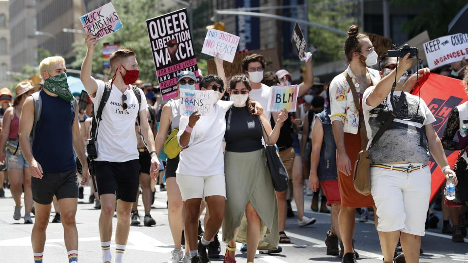 People hold signs as they participate in a queer liberation march for Black Lives Matter and against police brutality, Sunday, June 28, 2020, in New York.