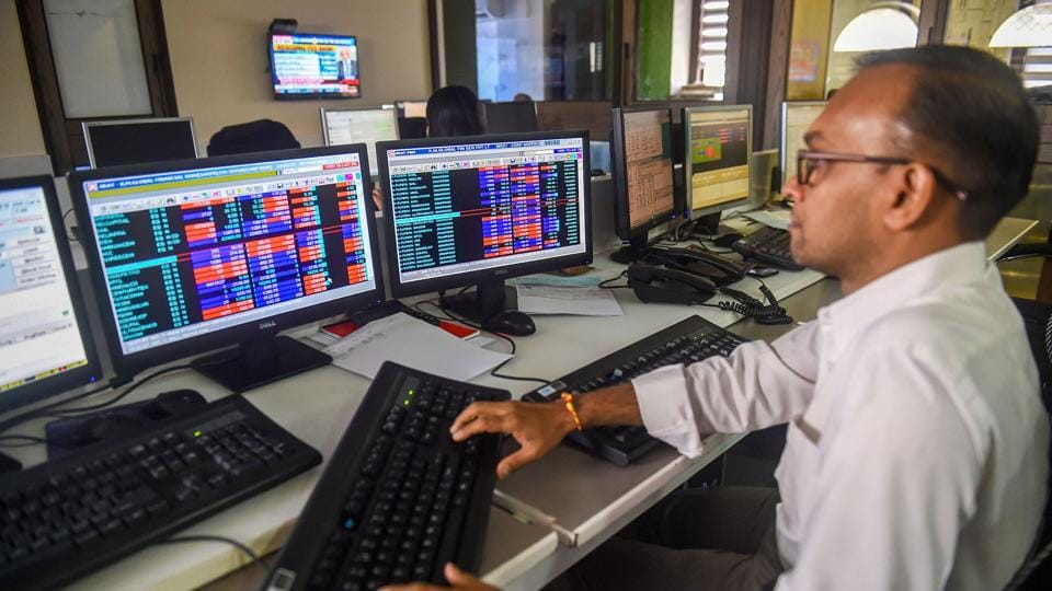 Traders monitor BSE index at a brokerage firm in Mumbai.